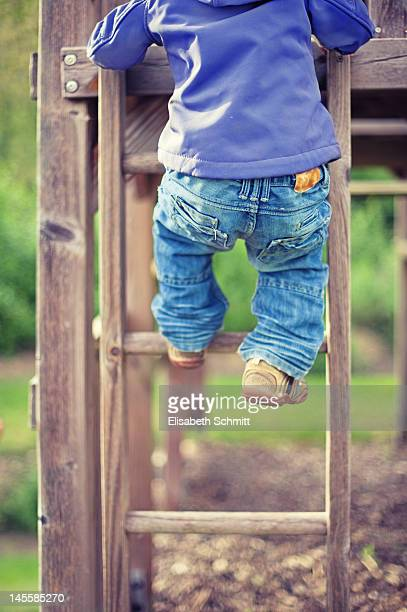 Toddler climbing up wooden ladder