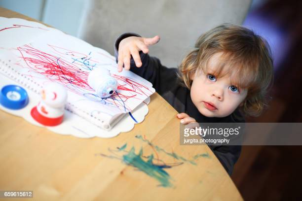 toddler coloring and making mess on the table - colouring book stock photos and pictures