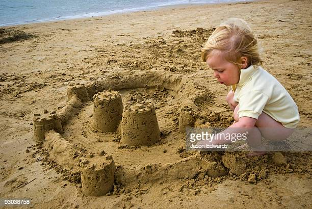 A toddler concentrates while building a sand castle on a beach.