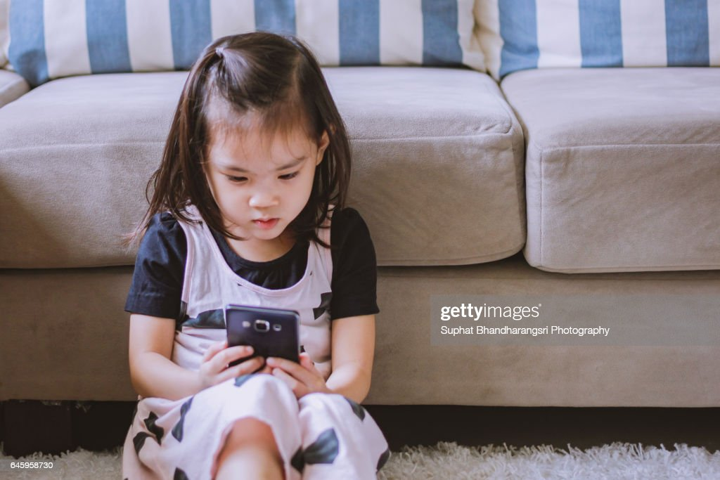 Toddler concentrating on smartphone screen : Stock Photo