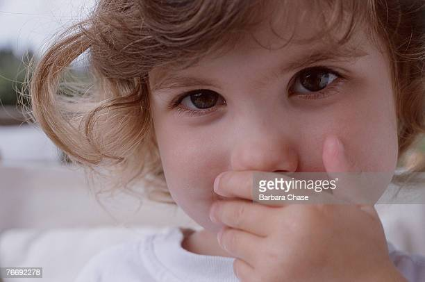 Toddler covering mouth with her hand