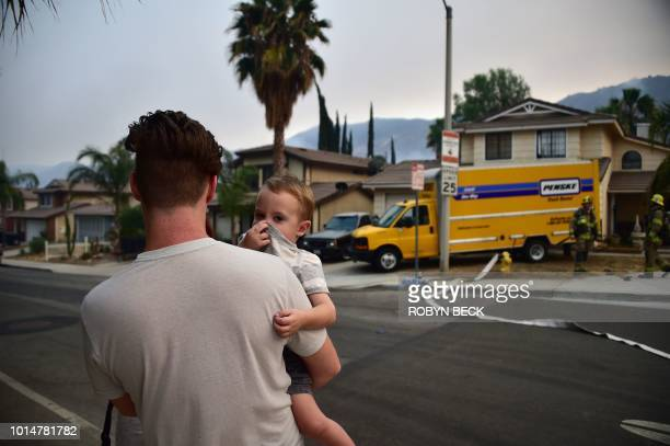 A toddler covers his nose at the Holy Fire in Lake Elsinore California southeast of Los Angeles on August 10 2018 Authorities battling massive...