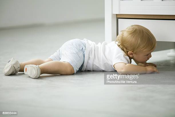 Toddler crawling on the ground, side view