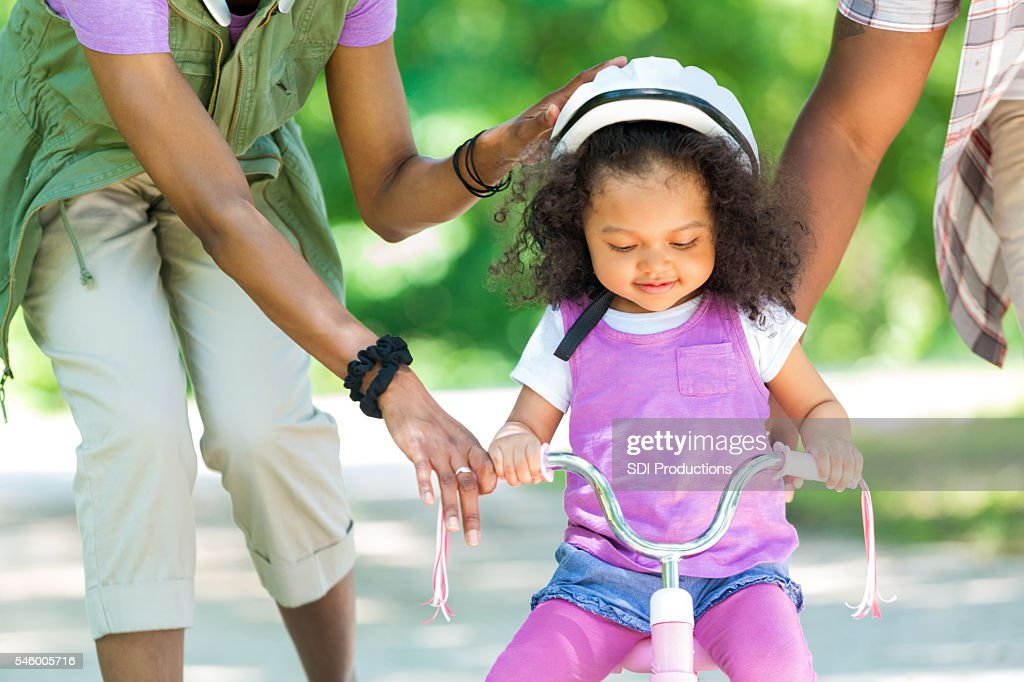 Toddler daughter learning to ride a tricycle : Stock Photo