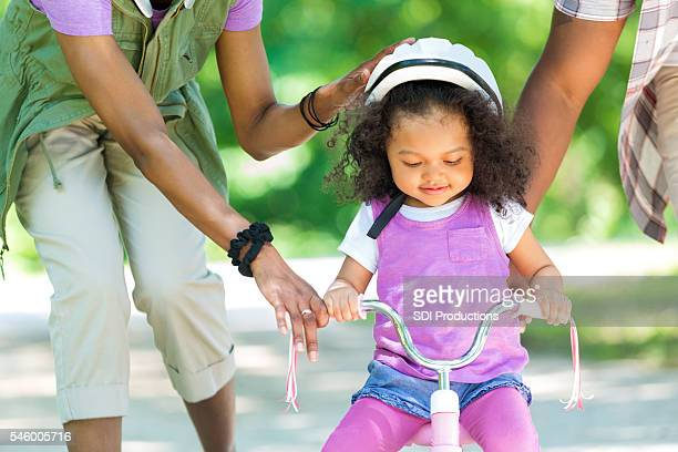 Toddler daughter learning to ride a tricycle