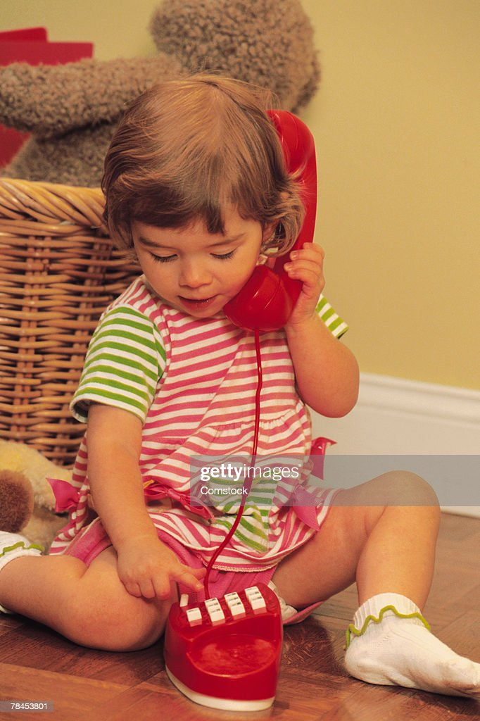 Toddler dialing toy telephone : Stockfoto