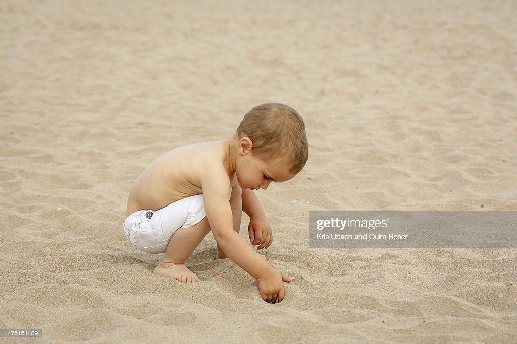 Toddler digging in sand with hand : Stock Photo