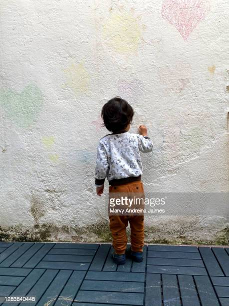 toddler drawing on wall with chalk - chalk wall stock pictures, royalty-free photos & images