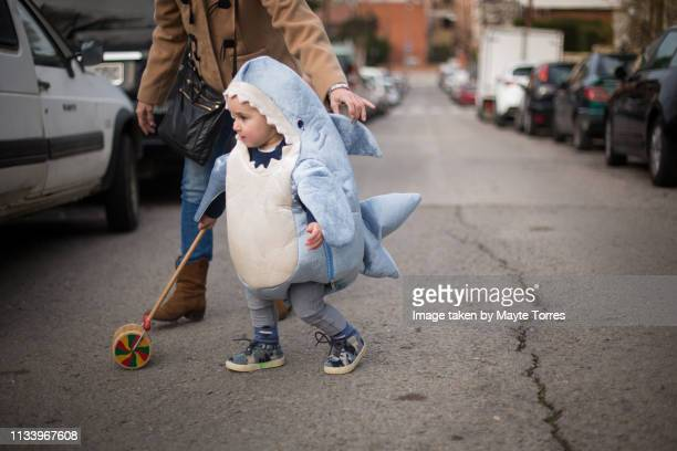 toddler dressed as a shark crossing the road with grandma - mamie humour photos et images de collection