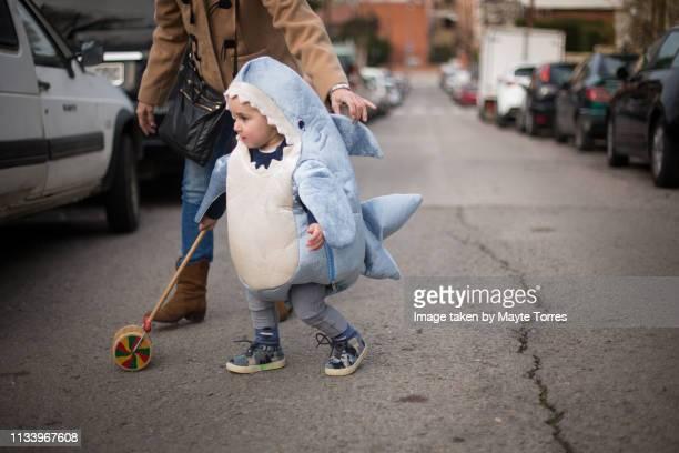 toddler dressed as a shark crossing the road with grandma - fish love stockfoto's en -beelden