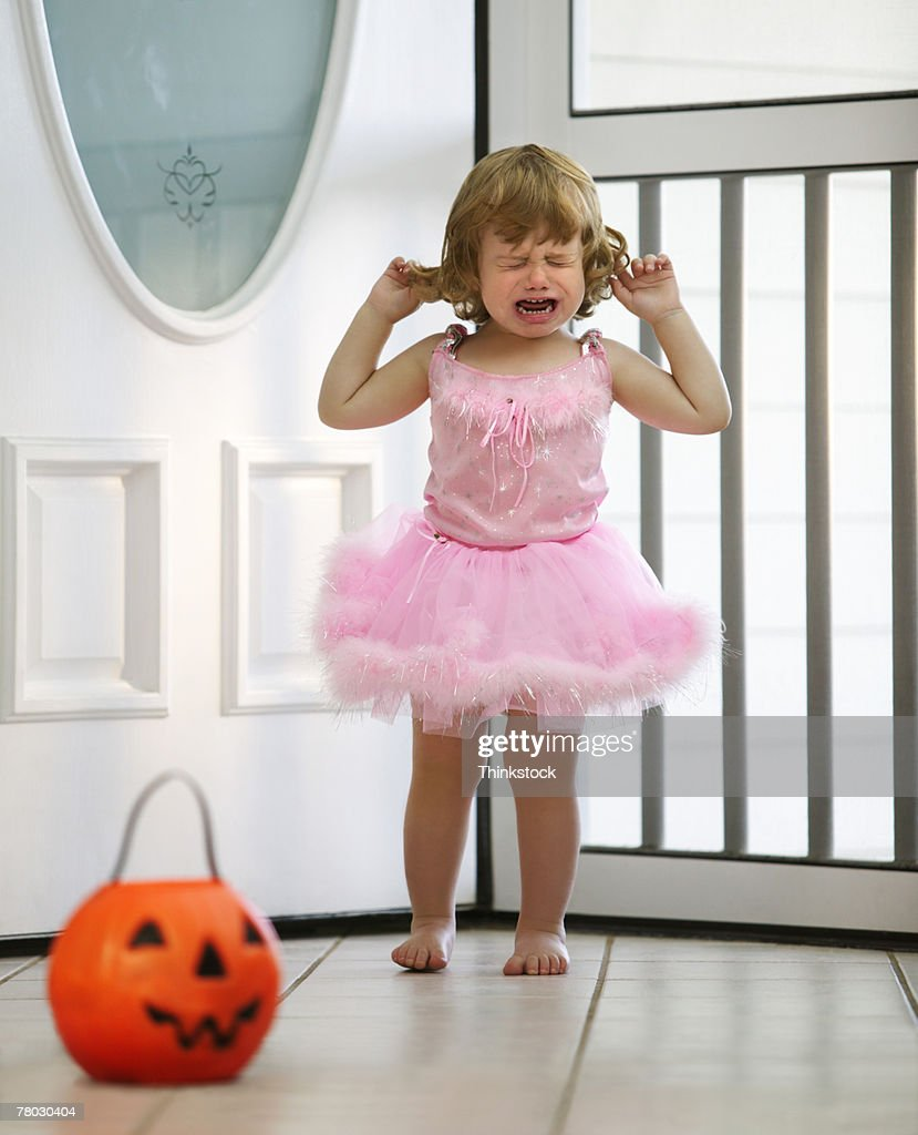 A toddler dressed in a ballet outfit for Halloween chooses candy from her pumpkin bucket : Stock Photo