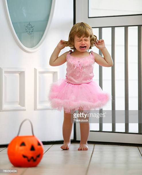 A toddler dressed in a ballet outfit for Halloween chooses candy from her pumpkin bucket
