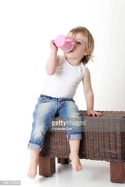 Toddler drinking from a baby cup