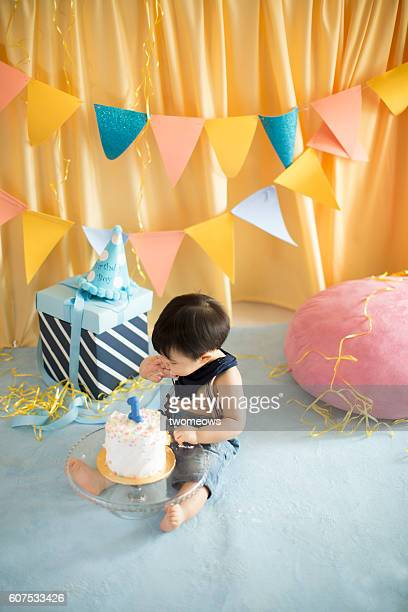 Toddler eating birthday cake.