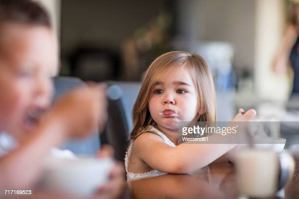 Toddler eating breakfast at table looking at brother