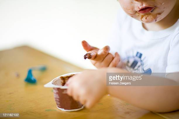 toddler eating chocolate dessert with hands