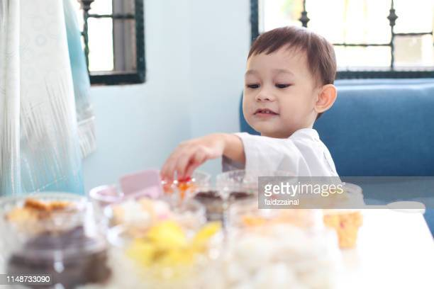 a toddler eating cookies on hari raya aidilfitri - traditional clothing stock pictures, royalty-free photos & images