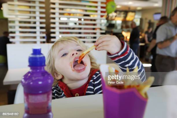 Toddler eating fast food in restaurant