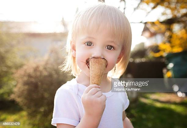 Toddler eating ice cream in waffle