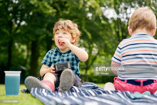 toddler eating in park - snack stock pictures, royalty-free photos & images