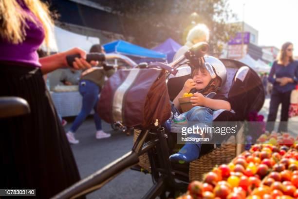 Toddler Eating Tomatoes in Bike Seat at Farmer's Market