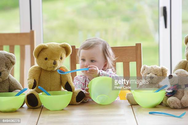Toddler feeding teddy bears at table