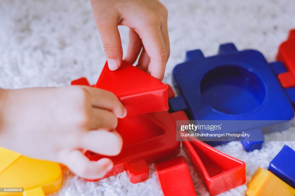 Toddler filling a red triangle block : Stock Photo