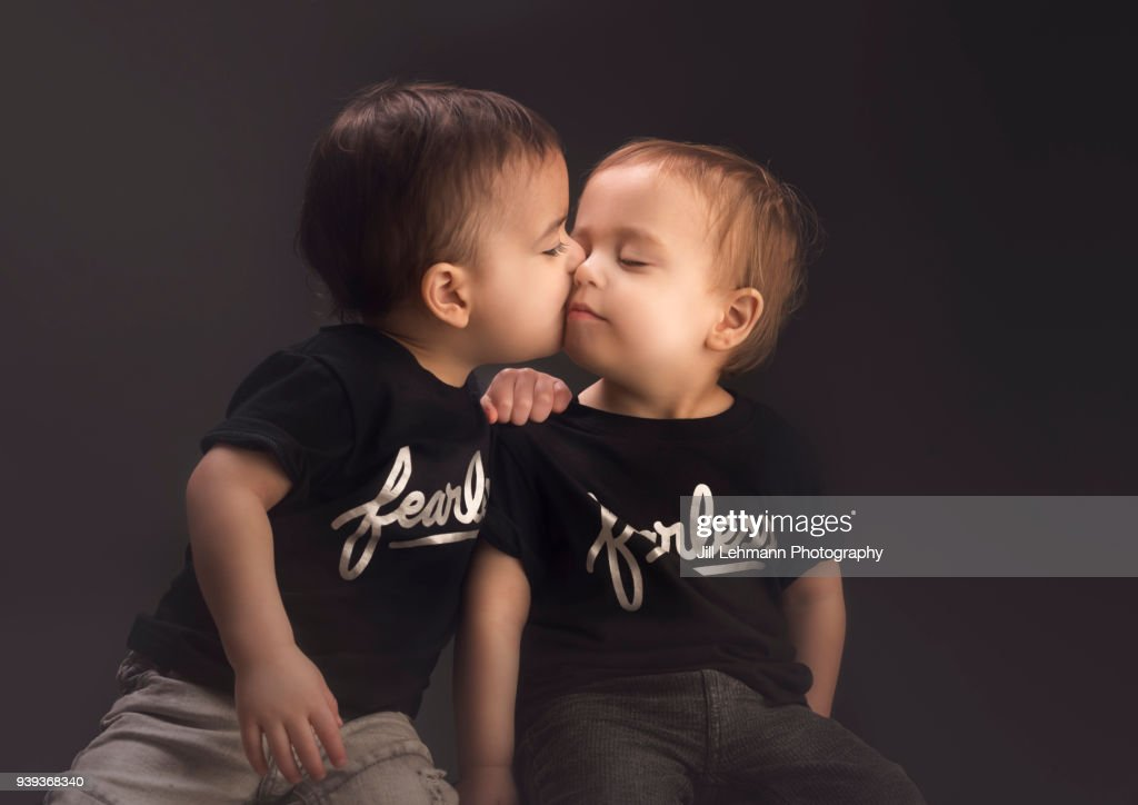 Toddler Fraternal Twins Embrace And Kiss Each Other In A Studio Shot