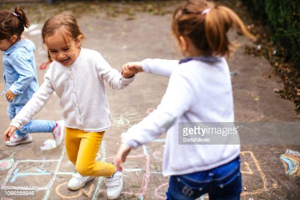 toddler friends playing hopscotch outdoors - hopscotch stock photos and pictures