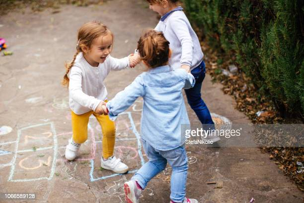 toddler friends playing hopscotch outdoors - giochi per bambini foto e immagini stock