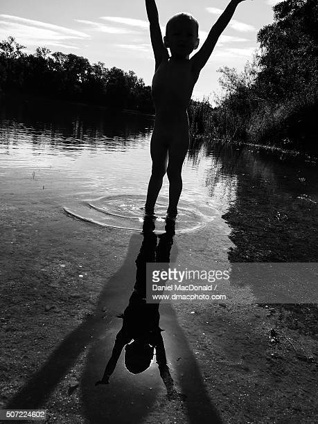 Toddler frolics in shallow river with silhouettes, shadows, and reflections