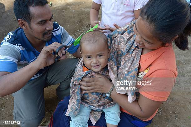 A toddler gets his hair cut at a shelter in Karo on February 7 2014 More than 30000 people have been displaced as Mount Sinabung continues spewing...