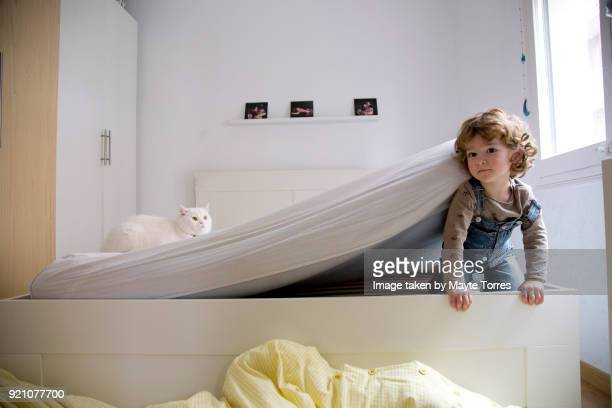 toddler getting out after hiding under the mattress - puss pics stock photos and pictures