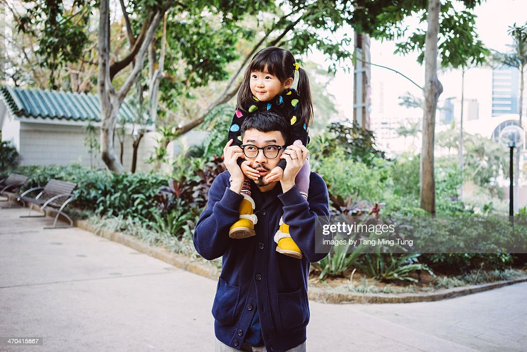 Toddler gilt sitting on dad's shoulders in park : Stock Photo