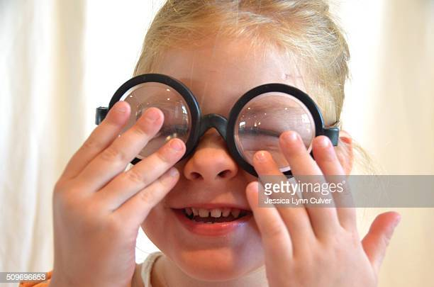 toddler girl acting silly wearing bottle glasses - lynn pleasant stock pictures, royalty-free photos & images