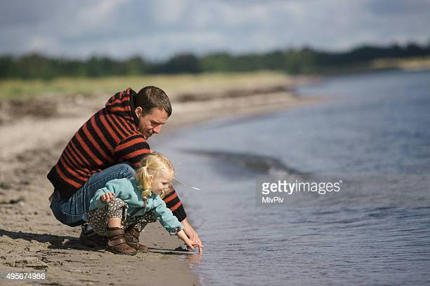 toddler girl and dad on the beach