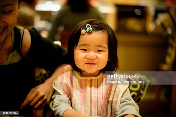 Toddler girl and young mom smiling on dining table
