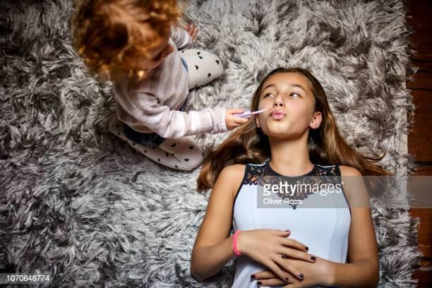Toddler girl applying lipstick for elder sister lying on flokati carpet