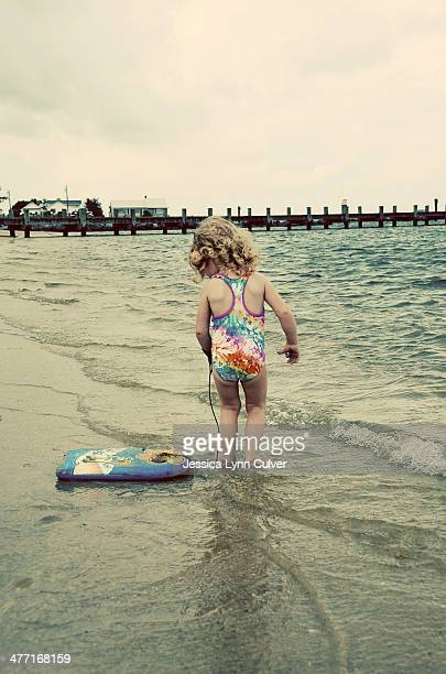 toddler girl at the beach with a boogie board - lynn pleasant stock pictures, royalty-free photos & images