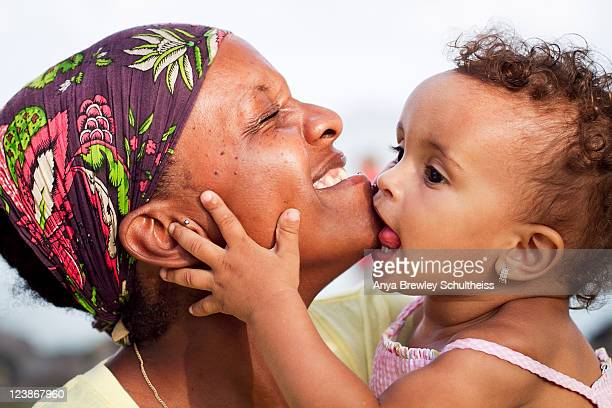 Toddler girl biting and kissing her mother's chin