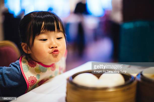 Toddler girl blowing on hot streaming dim sum buns