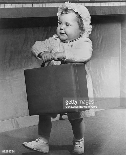 Toddler girl carrying suitcase