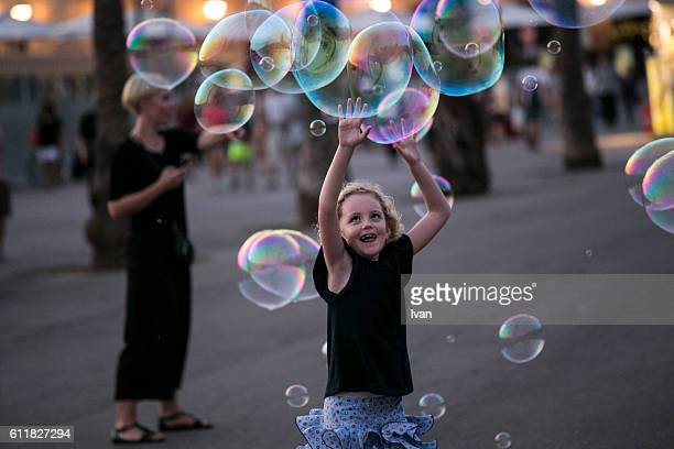 Toddler Girl Catching Bubbles Joyfully Outdoor