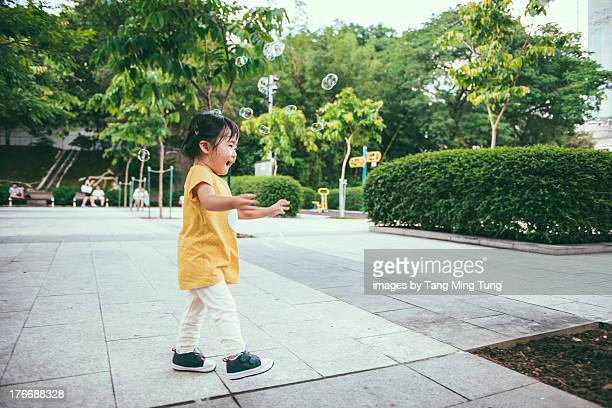 Toddler girl chasing and catching bubbles