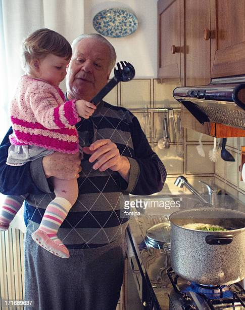 toddler girl cooking with her grandfather