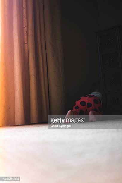 Toddler girl crawling behind curtains