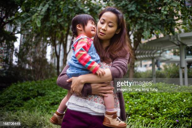 Toddler girl crying in mom's arms in park