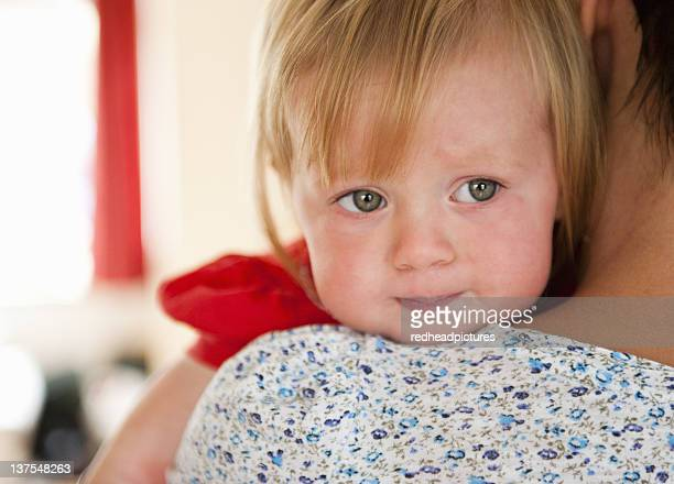 Toddler girl crying on mothers shoulder