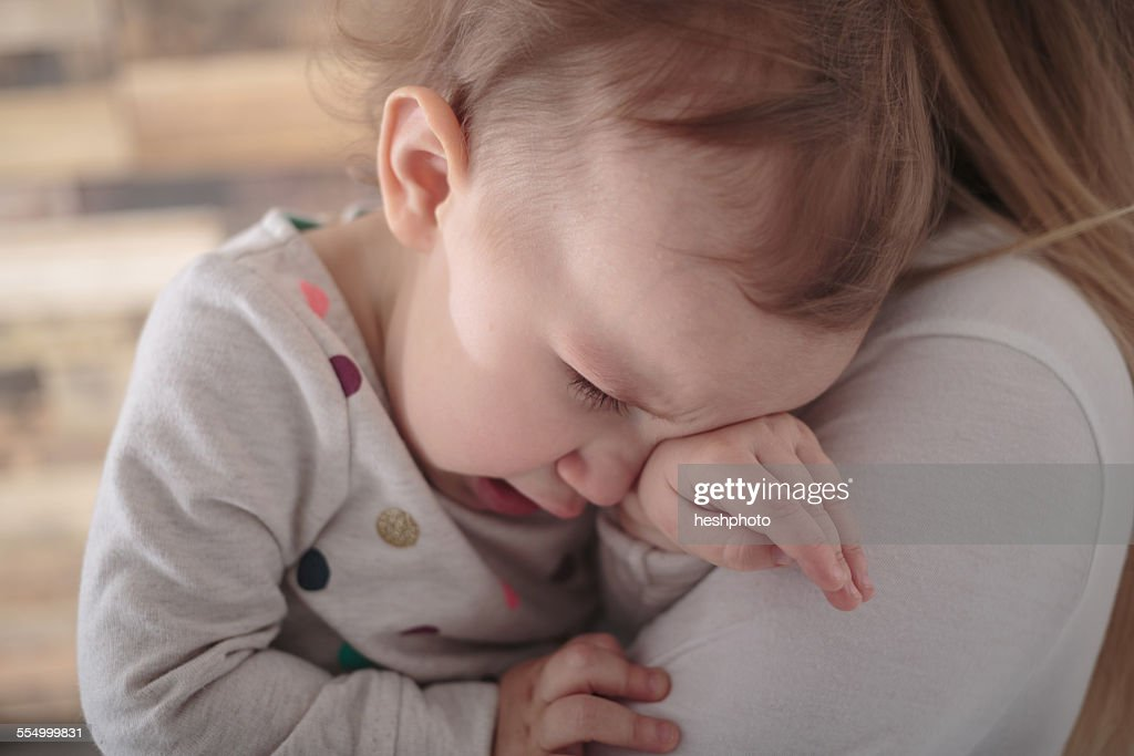 Toddler girl crying on mothers shoulder : Stock Photo