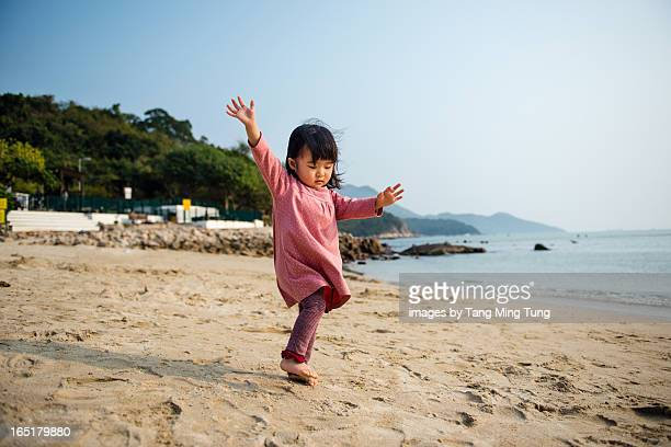 Toddler girl dancing on the beach